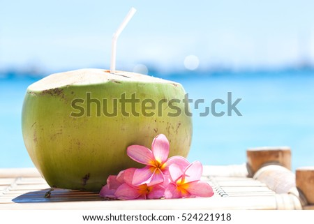 Tropical fresh coconut cocktail decorated plumeria on white beach