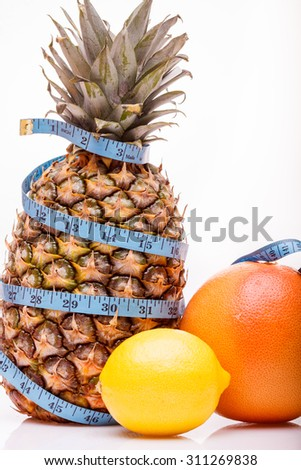 Tropical fresh fruits of one big pineapple yellow lemon and orange juicy grapefruit with blue measuring tape as diet symbol on white studio background closeup, vertical picture - stock photo