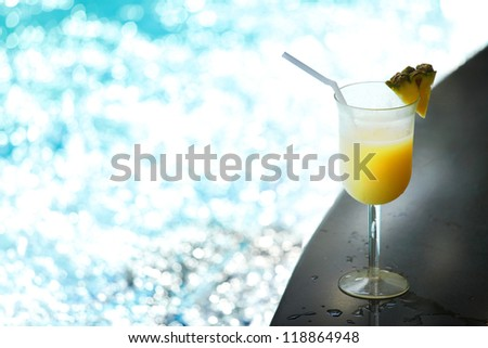 Tropical fruit alcohol cocktail near swimming pool - stock photo