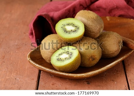 tropical fruit fresh sweet ripe kiwi on wooden plate - stock photo