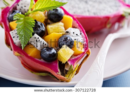 Tropical fruit salad served inside a dragon fruit - stock photo