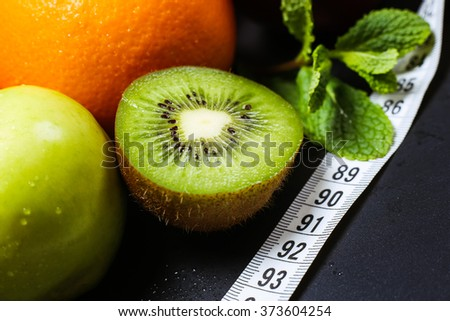 Tropical fruits and apples with measuring tape, symbolizing the concept of a healthy diet, weight loss, diet and vegetarianism - stock photo