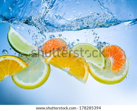 Tropical fruits fall deeply under water with a big splash - stock photo