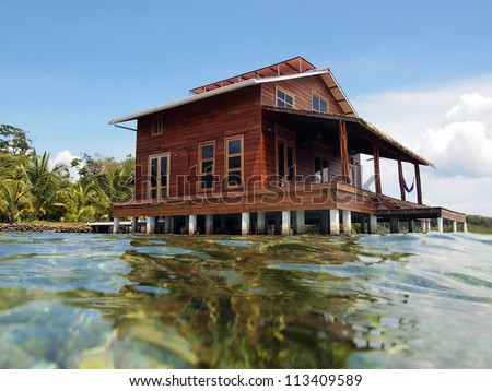Tropical home on stilts over water of the Caribbean sea
