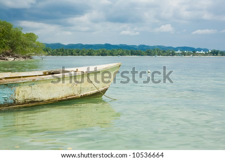 Tropical horizon with boat in the water - stock photo