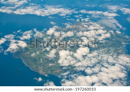 tropical islan under clouds from the air