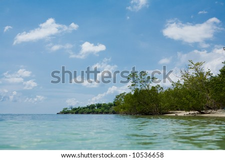 Tropical island around blue water and blue skies - stock photo