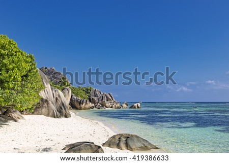 Tropical island beach white sand, rocks, palm trees, blue sky, famous anse source d'argent on La Digue, Seychelles islands