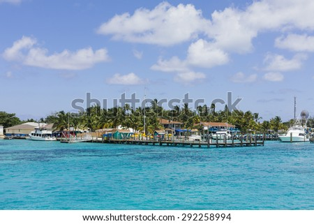 Tropical island harbor with boats and houses with turquoise water and blue sky - stock photo