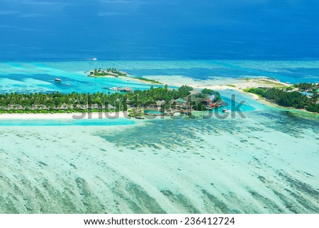 Tropical island on Bora Bora with water villas and coral reef. View from helicopter - stock photo