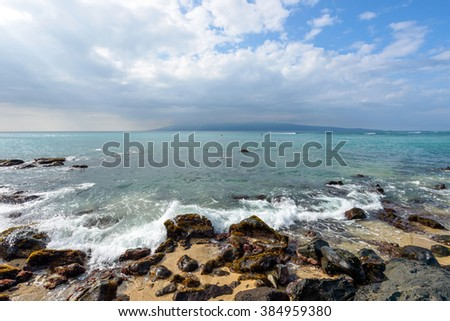 Tropical Island - Stormy clouds coming over a rocky tropical seashore, with blue ocean and a small island in the background. - stock photo