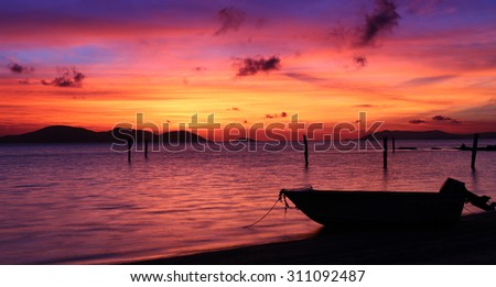 Tropical Island sunset with beach and boat in silhouette, with orange and blue tones