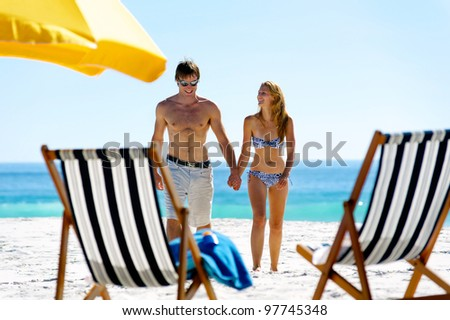 tropical island vacation summer beach couple walking holding hands and laughing together in the sun - stock photo