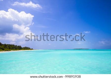 tropical island with long beach, palms, blue sky, turquoise, sea - stock photo