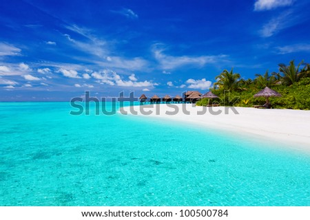 Tropical island with palm trees and villas over turquoise lagoon - stock photo