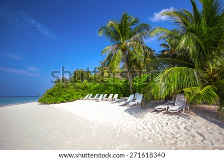 Tropical island with sandy beach, palm trees, overwater bungalows and tourquise clear water - stock photo