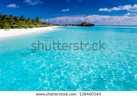 Tropical island with sandy beach with palm trees and pristine water - stock photo