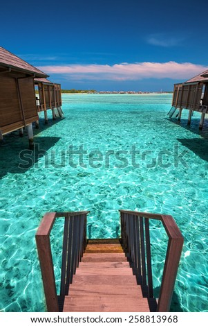 Tropical island with sandy beach with palm trees and tourquise clear water - stock photo