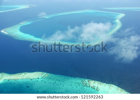 Tropical islands in Indian ocean Maldives from above with sky clouds