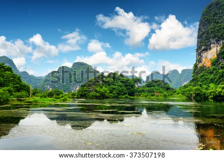 Tropical lake among karst towers at Ninh Binh Province, Vietnam. Blue sky with clouds is visible in background. Ninh Binh Province is a popular tourist destination of Asia.