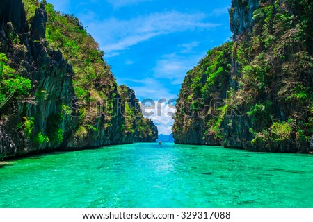 Tropical landscape with rock islands, lonely boat and crystal clear water, Palawan, Philippines - stock photo