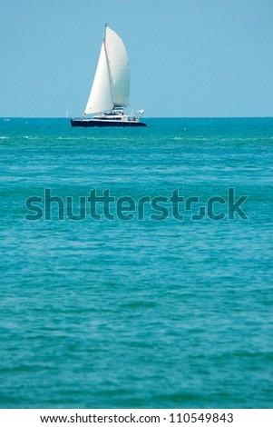 Tropical landscape with sailboat