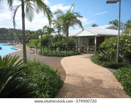 Tropical Landscaping - Lush Tropical Pathway with Planting and Palm Trees - stock photo
