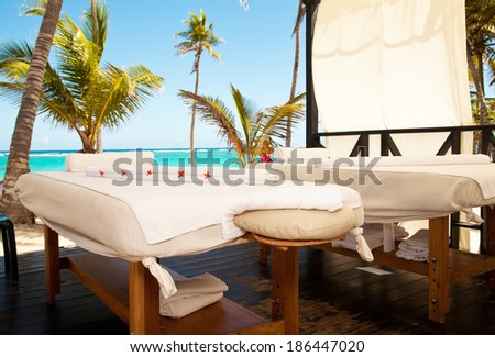 Tropical massage setting. Spa salon at the beach of tropical island - health care background. - stock photo