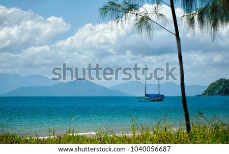 tropical Mission Beach with turquoise waters and clouds in the sky