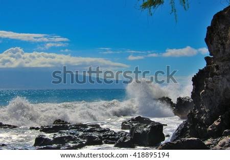 Tropical ocean beach waves breaking onto lava rocks located in beautiful travel destination Maui, Hawaii - stock photo