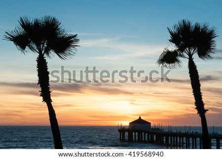 Tropical palms sway in breeze under colorful sunset on Manhattan Beach with famous pier silhouette Californian beaches