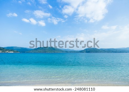 Tropical paradise beach and clear blue water with lush jungle islands on the horizon, Iriomote Island of the Yaeyama Islands, Okinawa, Japan - stock photo