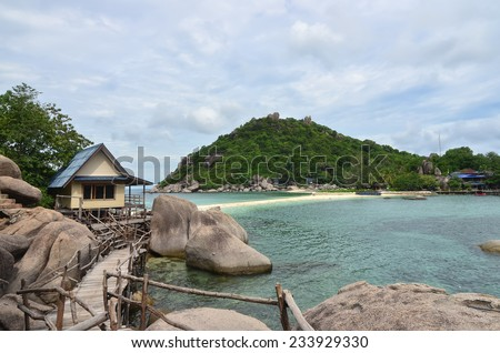 Tropical paradise - lagoon and white sand beach at a small island with stunning green hills at the background - stock photo