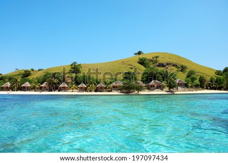 Tropical Paradise with Turquoise Water and Lush Greenery - Lovely island with bungalows and hill - stock photo