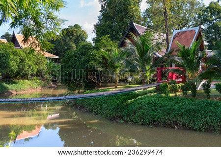 Tropical park with wooden long rope pendant bridge cross the stream  - stock photo