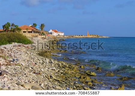 Tropical pebble beach with small houses and calm blue sea. Idyllic island with exotic ocean shore.  Sunny tropical day near the ocean.