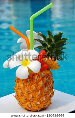 Tropical pineapple cocktail. Drink on the background of the pool. - stock photo