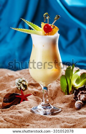Tropical pineapple milkshake on the sand and leaves of aloe and decor Cherry beach sea ocean of ice, cool, sea, bar, alcohol, Pina Colada still life milk shake  - stock photo