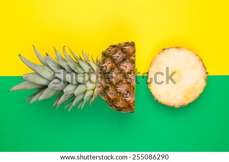 Tropical pineapples on green and yellow background - stock photo