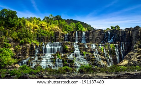 Tropical rainforest landscape panorama with flowing Pongour waterfall under blue sky. Da Lat, Vietnam - stock photo