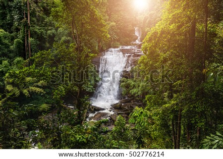 Tropical rainforest landscape with beautiful waterfall, rocks