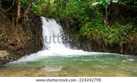 Tropical rainforest landscape with beautiful waterfall, rocks and jungle plants. Vang Vieng, Laos (kaeng nyui waterfall) - stock photo