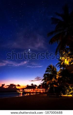 Tropical resort at night, beautiful nighttime scene of a romantic beach, peaceful island landscape - stock photo