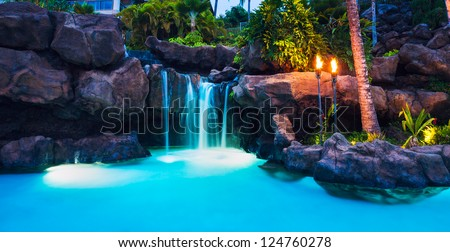 Tropical Resort Pool and Waterfall at Sunset in Hawaii - stock photo