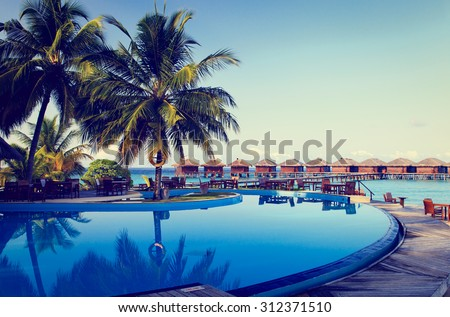 Tropical resort swimming pool and cafe bar near the beach - stock photo