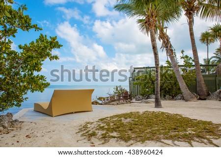 Tropical resort with chaise longs and hammocks near palms on sandy beach, Key West, Florida, USA - stock photo