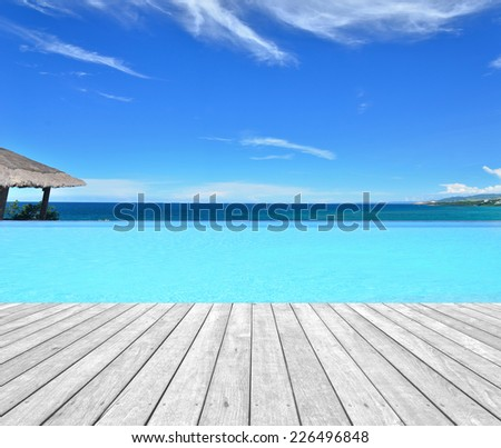 Tropical resorts hotel infinity swimming pool with empty wooden platform - stock photo