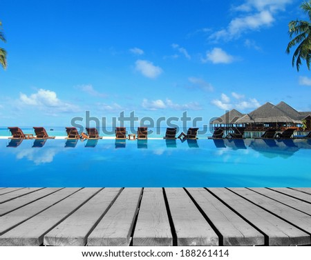 Tropical resorts swimming pool with empty wooden platform -- Summer holidays concept - stock photo