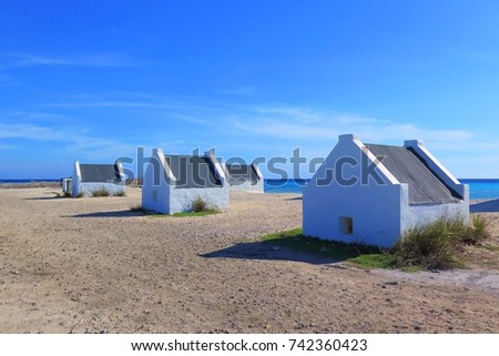 Tropical sandy beach with small white houses. Exotic island with beach and stone buildings. White old architecture on the beach under the blue sky.