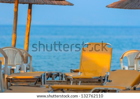 Tropical scene with Parasol and beach beds